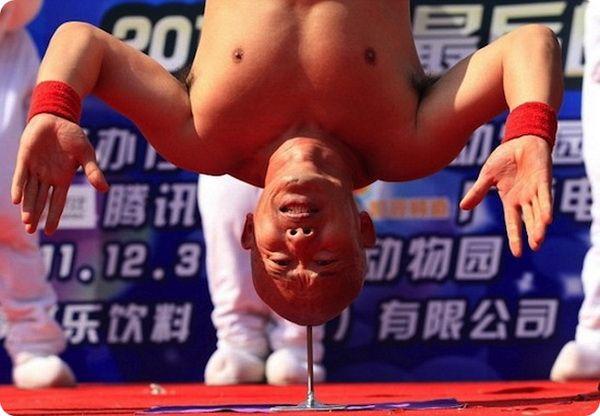 Китаец Ли Ксин стоит вниз головой на гвозде
